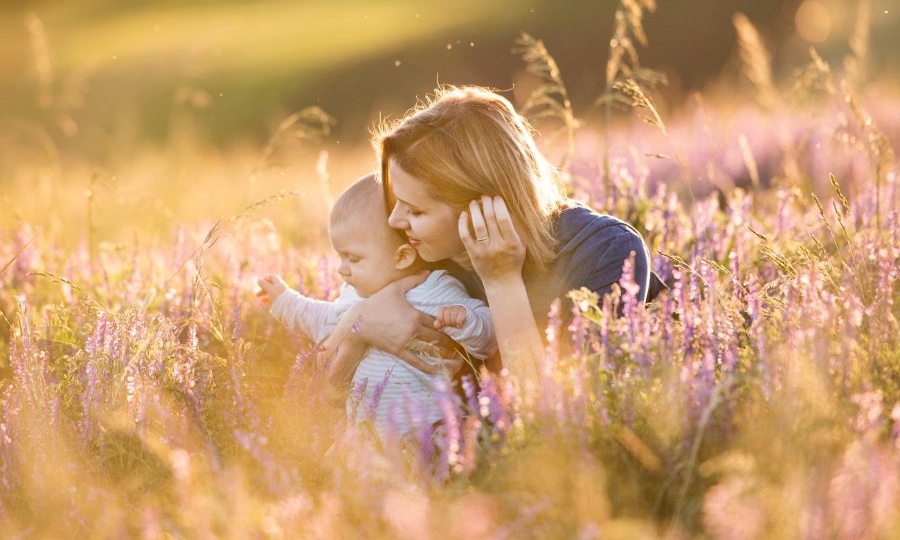 Bebé com mãe num campo de flores