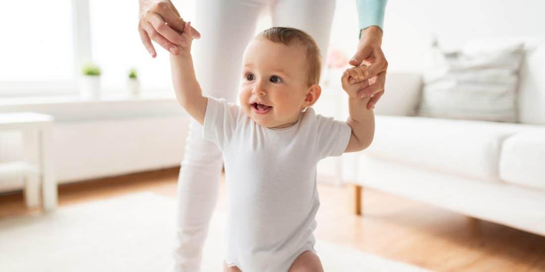 Bebé a andar pelas mãos da mãe